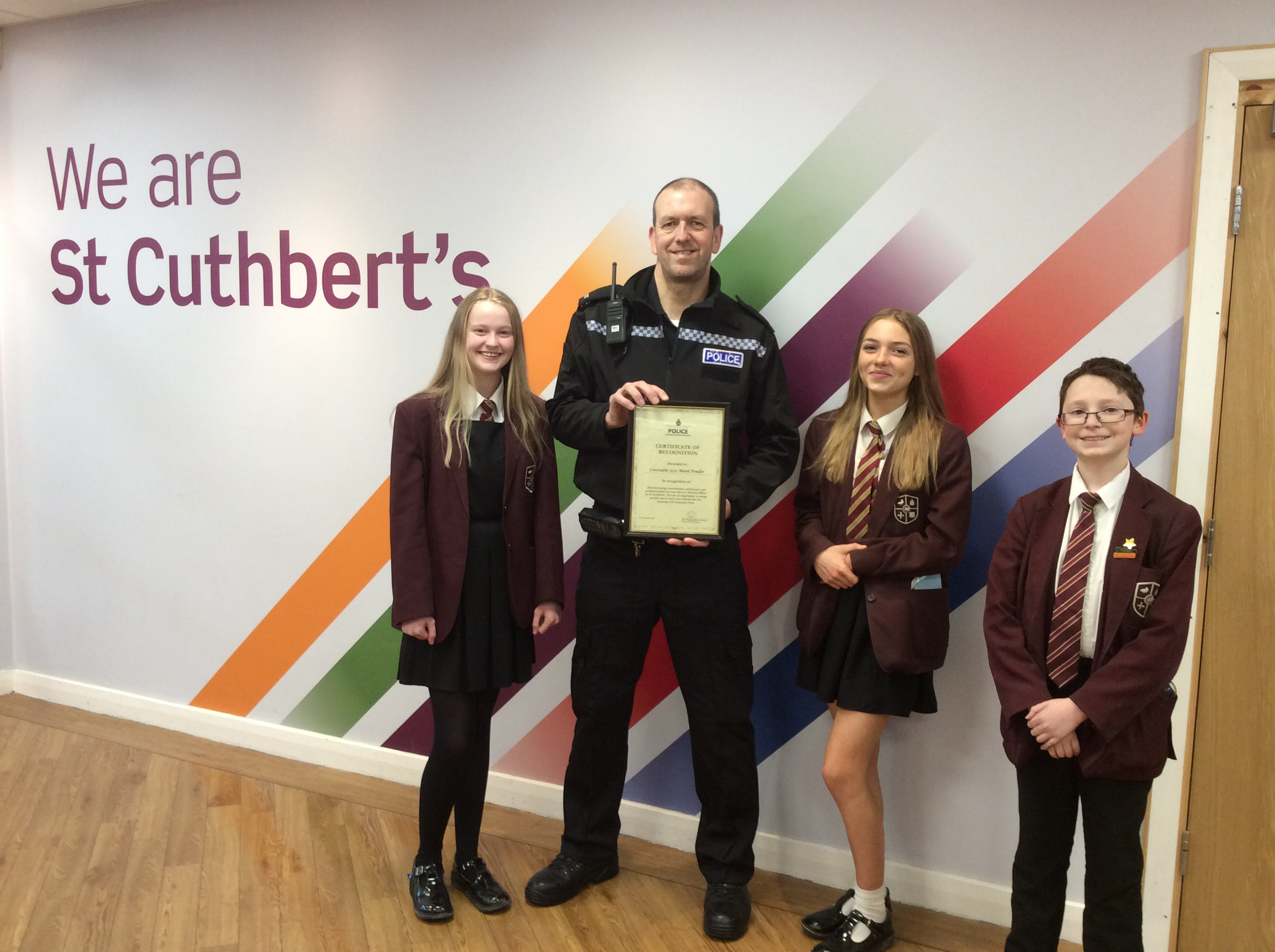 PC Pender receiving his certificate from students Holly, Millie and Leon